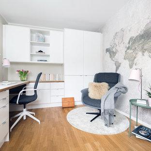 Cette photo montre un bureau scandinave de taille moyenne avec un sol en bois clair, un bureau intégré, un sol beige, un mur beige et aucune cheminée.