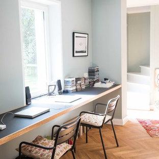 Mittelgroßes Klassisches Arbeitszimmer ohne Kamin mit Arbeitsplatz, grauer Wandfarbe, braunem Holzboden und Einbau-Schreibtisch in Berlin