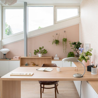 Design ideas for a mid-sized contemporary study room in Berlin with pink walls, light hardwood floors, a built-in desk and beige floor.