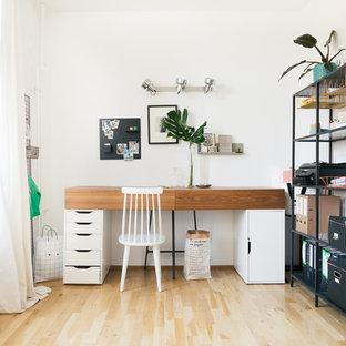 Kleines Mid-Century Arbeitszimmer ohne Kamin mit weißer Wandfarbe, freistehendem Schreibtisch, Arbeitsplatz, hellem Holzboden und braunem Boden in Berlin
