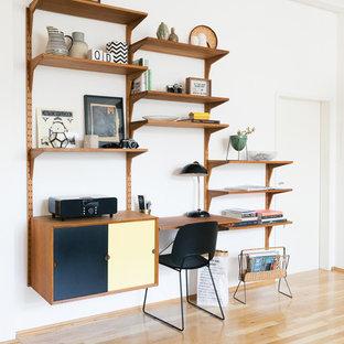 Kleines Retro Arbeitszimmer ohne Kamin mit Arbeitsplatz, weißer Wandfarbe, braunem Holzboden, Einbau-Schreibtisch und braunem Boden in Berlin