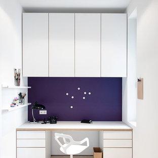 Cette image montre un bureau nordique de taille moyenne avec un sol en bois clair, un bureau intégré, un mur violet et aucune cheminée.