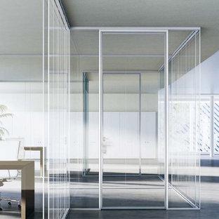 Ispirazione per un ampio atelier minimalista con pareti bianche, scrivania autoportante, pavimento in cemento e pavimento grigio