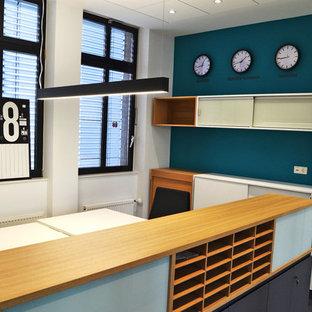 他の地域の巨大なコンテンポラリースタイルのおしゃれな書斎 (緑の壁、ラミネートの床、自立型机、茶色い床) の写真