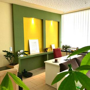 Immagine di un grande ufficio minimal con pareti verdi, pavimento con piastrelle in ceramica, scrivania autoportante e pavimento beige