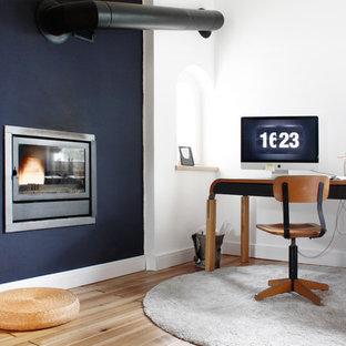 Modelo de despacho nórdico, grande, con paredes azules, suelo de madera en tonos medios, chimenea tradicional, escritorio independiente y marco de chimenea de metal