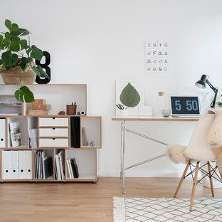 Mittelgroßes Nordisches Arbeitszimmer ohne Kamin mit Arbeitsplatz, weißer Wandfarbe, hellem Holzboden, freistehendem Schreibtisch und braunem Boden in Berlin