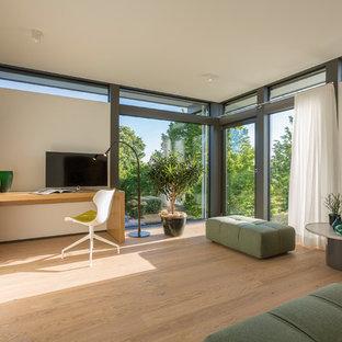 Großes Modernes Arbeitszimmer mit weißer Wandfarbe, hellem Holzboden, freistehendem Schreibtisch und beigem Boden in Sonstige