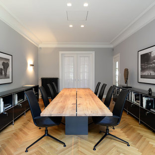 Diseño de despacho contemporáneo, grande, con paredes grises, suelo de madera clara y escritorio independiente