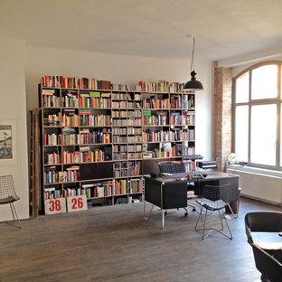 Modernes Lesezimmer mit weißer Wandfarbe, dunklem Holzboden, freistehendem Schreibtisch und braunem Boden in Dortmund