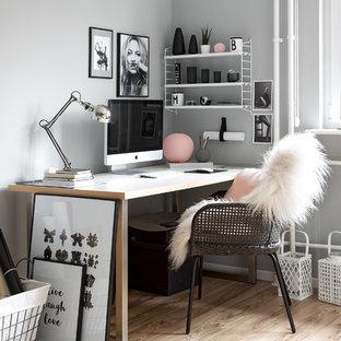 Exempel på ett litet skandinaviskt hobbyrum, med grå väggar, ljust trägolv, ett fristående skrivbord och brunt golv