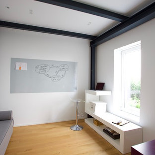 Idee per un piccolo ufficio moderno con pareti bianche, parquet chiaro, scrivania autoportante e pavimento giallo