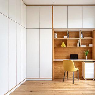 Modernes Arbeitszimmer mit Arbeitsplatz, hellem Holzboden, Einbau-Schreibtisch, weißer Wandfarbe und beigem Boden in Berlin