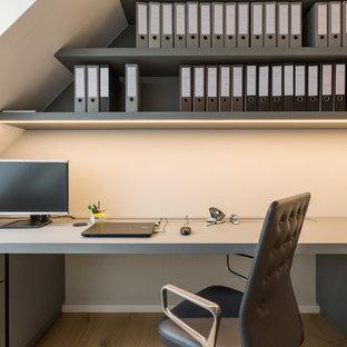 ミュンヘンの広いコンテンポラリースタイルのおしゃれな書斎 (ベージュの壁、塗装フローリング、暖炉なし、造り付け机、茶色い床) の写真