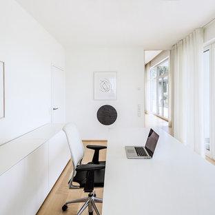Mittelgroßes Modernes Arbeitszimmer ohne Kamin mit Arbeitsplatz, weißer Wandfarbe, hellem Holzboden, freistehendem Schreibtisch und beigem Boden in Köln