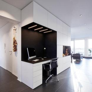Mittelgroßes Modernes Arbeitszimmer ohne Kamin mit Arbeitsplatz, weißer Wandfarbe, Einbau-Schreibtisch und schwarzem Boden in Frankfurt am Main