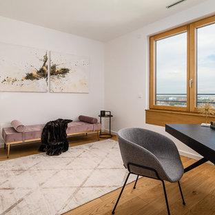 Mittelgroßes Modernes Arbeitszimmer ohne Kamin mit Arbeitsplatz, weißer Wandfarbe, braunem Holzboden, freistehendem Schreibtisch und braunem Boden in München