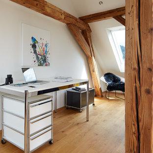 Mittelgroßes Modernes Arbeitszimmer ohne Kamin mit Arbeitsplatz, weißer Wandfarbe, braunem Holzboden, freistehendem Schreibtisch und braunem Boden in Hamburg