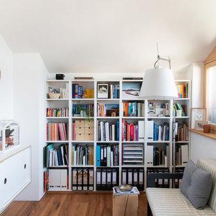 Mittelgroßes Nordisches Arbeitszimmer mit weißer Wandfarbe, braunem Holzboden, braunem Boden und Einbau-Schreibtisch in München
