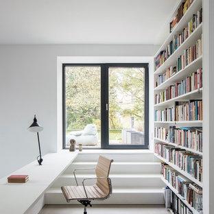 Ejemplo de despacho actual, pequeño, con paredes blancas, suelo de cemento, escritorio empotrado y suelo gris