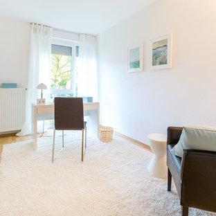 Пример оригинального дизайна: рабочее место среднего размера в скандинавском стиле с белыми стенами, полом из ламината, отдельно стоящим рабочим столом и коричневым полом без камина