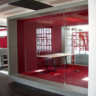 Large industrial home studio in Cologne with red walls, carpet, no fireplace, a freestanding desk and red floor.