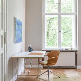Großes Modernes Arbeitszimmer ohne Kamin mit Studio, grauer Wandfarbe, hellem Holzboden und freistehendem Schreibtisch in Berlin