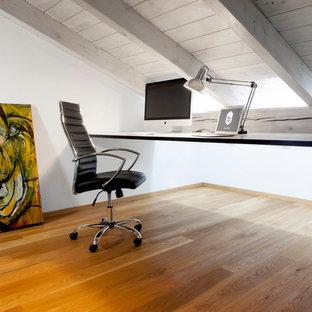 Cette photo montre un grand bureau scandinave avec un mur blanc, un sol en bois clair, un poêle à bois, un manteau de cheminée en métal et un sol marron.