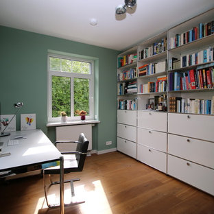Réalisation d'un bureau vintage de taille moyenne avec un mur vert, un sol en bois clair, un bureau indépendant, aucune cheminée et un sol marron.