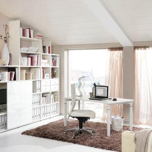Mittelgroßes Skandinavisches Arbeitszimmer ohne Kamin mit Arbeitsplatz, beiger Wandfarbe, freistehendem Schreibtisch und weißem Boden in Dresden
