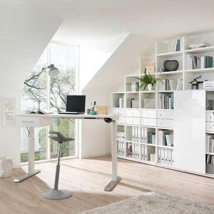 Mittelgroßes Modernes Arbeitszimmer ohne Kamin mit Arbeitsplatz, weißer Wandfarbe, hellem Holzboden, freistehendem Schreibtisch und beigem Boden in Dresden