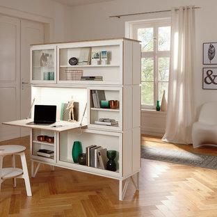 Mittelgroßes Modernes Arbeitszimmer Mit Arbeitsplatz, Weißer Wandfarbe,  Braunem Holzboden, Freistehendem Schreibtisch Und Braunem