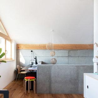Nordisches Arbeitszimmer mit weißer Wandfarbe, braunem Holzboden, freistehendem Schreibtisch und braunem Boden in München