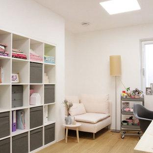 Modernes Nähzimmer mit weißer Wandfarbe, braunem Holzboden und Einbau-Schreibtisch in München