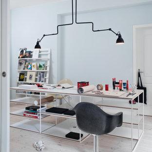 Skandinavisches Arbeitszimmer mit Arbeitsplatz, hellem Holzboden und weißem Boden in Berlin