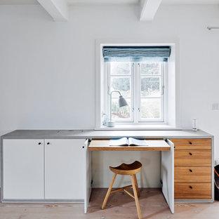 Modernes Arbeitszimmer mit weißer Wandfarbe, hellem Holzboden, Einbau-Schreibtisch, beigem Boden und freigelegten Dachbalken in Hamburg
