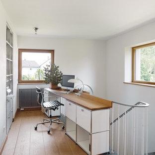 Modernes Arbeitszimmer mit Arbeitsplatz, weißer Wandfarbe, braunem Holzboden und Einbau-Schreibtisch in Berlin