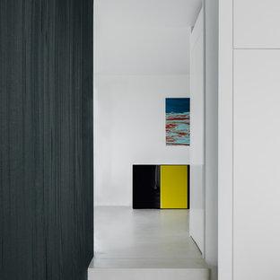 Ispirazione per un grande ufficio moderno con pareti bianche, pavimento in cemento, stufa a legna, cornice del camino in intonaco, scrivania autoportante e pavimento grigio