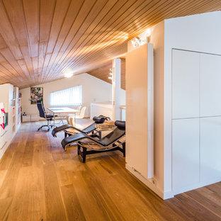 Идея дизайна: огромный кабинет в современном стиле с белыми стенами, паркетным полом среднего тона, отдельно стоящим рабочим столом, библиотекой, фасадом камина из штукатурки и коричневым полом без камина