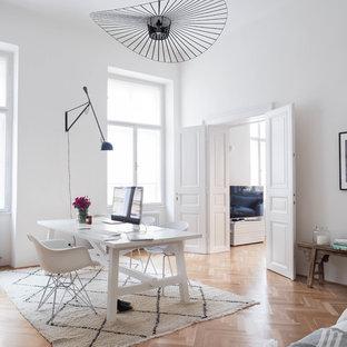 Создайте стильный интерьер: рабочее место среднего размера в скандинавском стиле с отдельно стоящим рабочим столом, белыми стенами, паркетным полом среднего тона и коричневым полом без камина - последний тренд