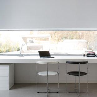 Idee per un grande ufficio minimalista con pareti bianche, pavimento in cemento, scrivania incassata e nessun camino