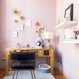 Idee per un piccolo ufficio nordico con pareti rosa, pavimento in legno massello medio e scrivania autoportante