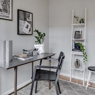 Inspiration för mellanstora nordiska hemmabibliotek, med grå väggar, ljust trägolv och ett fristående skrivbord