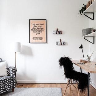 Idéer för ett nordiskt arbetsrum, med vita väggar, mellanmörkt trägolv, ett fristående skrivbord och brunt golv