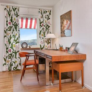 Idéer för mellanstora skandinaviska hemmabibliotek, med vita väggar, mellanmörkt trägolv och ett fristående skrivbord
