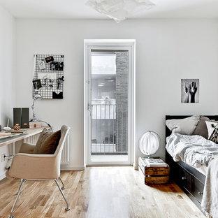 Exempel på ett mellanstort minimalistiskt arbetsrum, med vita väggar, mellanmörkt trägolv och ett fristående skrivbord