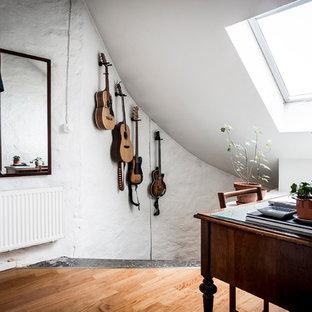 Foto på ett litet skandinaviskt arbetsrum, med vita väggar