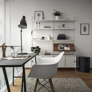 Photo of a medium sized scandinavian home office and library in Stockholm with white walls, medium hardwood flooring and a freestanding desk.