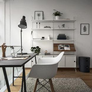 Skandinavisk inredning av ett mellanstort arbetsrum, med vita väggar, mellanmörkt trägolv och ett fristående skrivbord