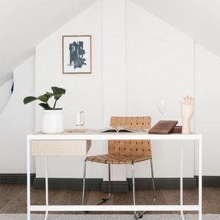 Exempel på ett nordiskt arbetsrum, med vita väggar, ett fristående skrivbord och brunt golv